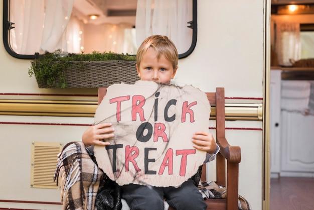 Medium shot boy holding trick or treat sign