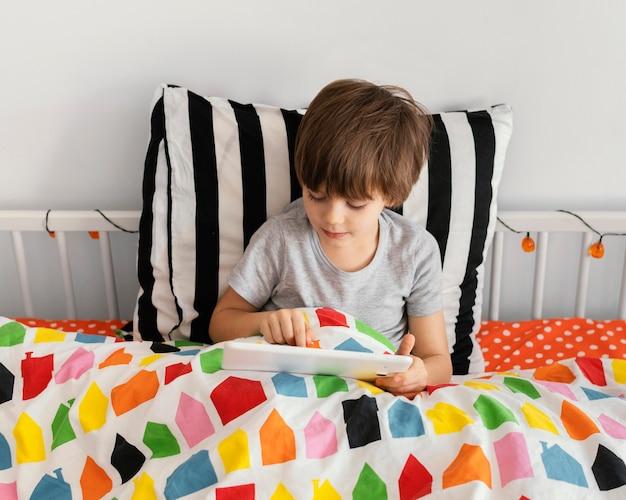 태블릿 침대에서 중간 샷된 소년