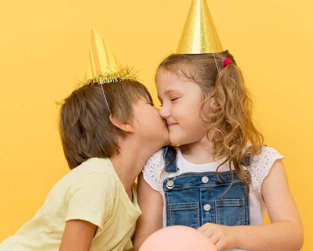 ミディアムショットの男の子が頬に女の子にキス