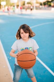 Medium shot of boy playing basketball