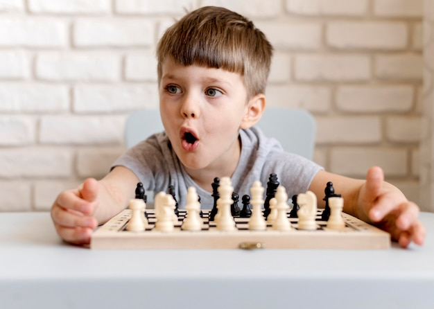 Medium shot boy playing chess