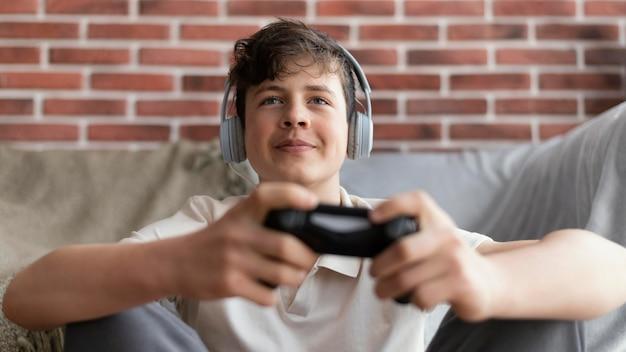 Мальчик среднего выстрела, играющий с контроллером
