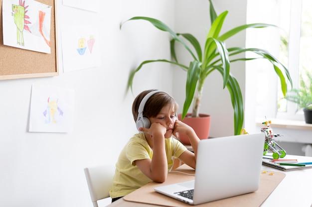 Ragazzo di tiro medio seduto alla scrivania con il computer portatile