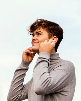 Medium shot boy wearing earphones