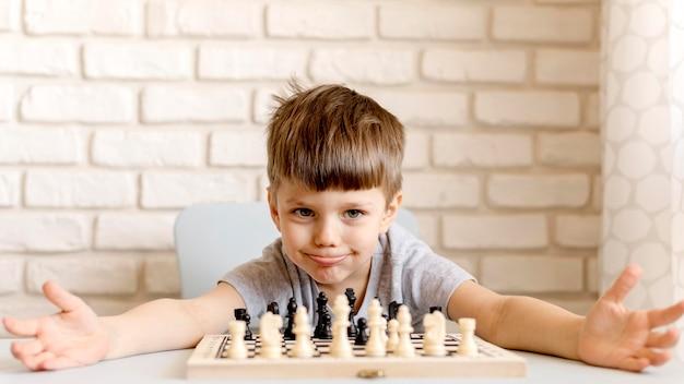 チェスのゲームでミディアムショットの少年