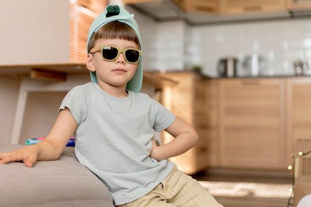 Colpo medio ragazzo con occhiali da sole