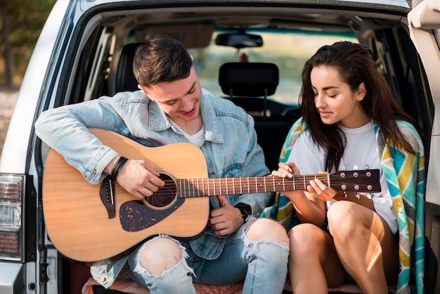 ギターを弾くミディアムショットのボーイフレンド