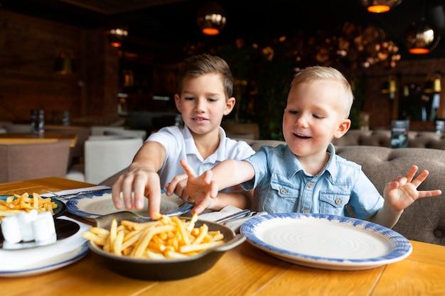 Ragazzi del colpo medio che mangiano patatine fritte