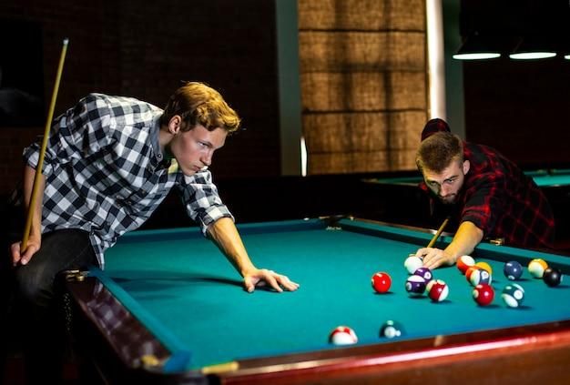 Medium shot boys playing billiard together