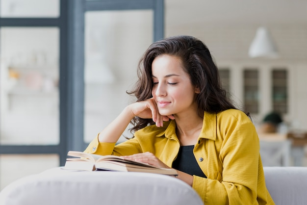 Medium shot brunette woman reading indoors