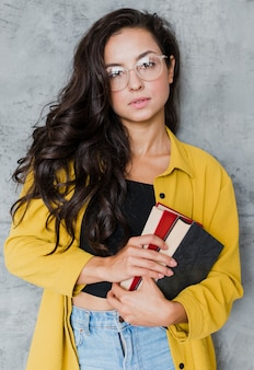 Medium shot brunette woman with glasses posing