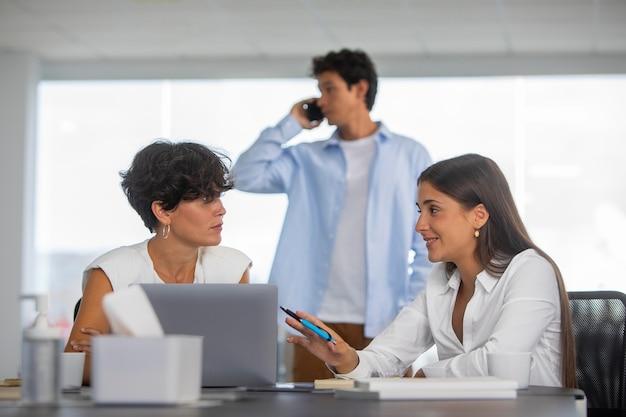 노트북과 중간 샷 비즈니스 사람들