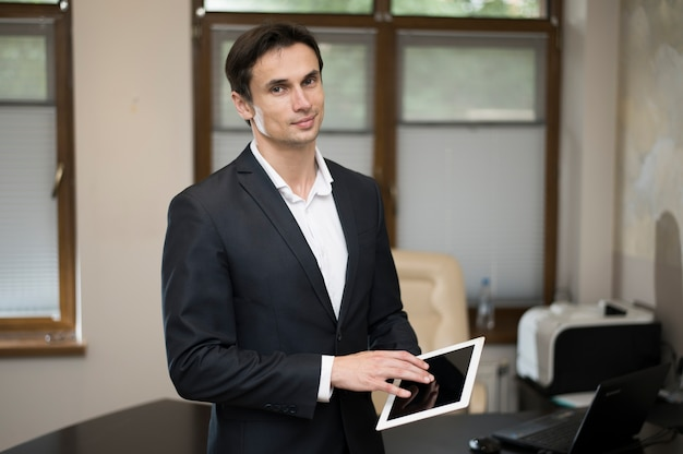 Medium shot of businessman using tablet