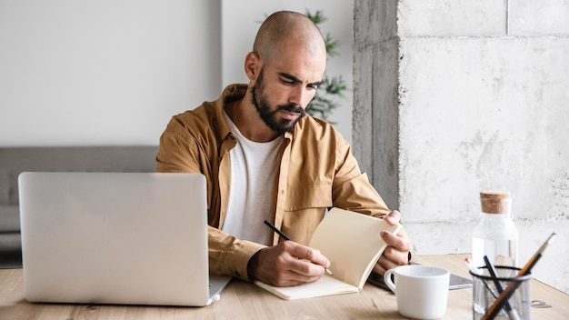 Средний снимок занятого человека, пишущего на ноутбуке