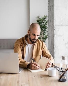 Средний снимок занятого человека, пишущего