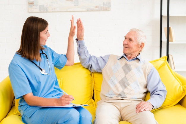 Medium shot caregiver high fiving with old man