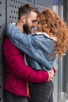 Medium shot casual couple hugging outdoors