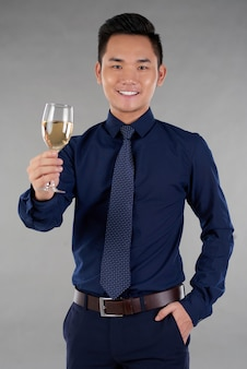 Medium shot of cheerful man toasting with a glass of white wine