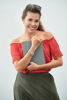 Medium shot of cheerful woman with tablet pc clasped to her chest