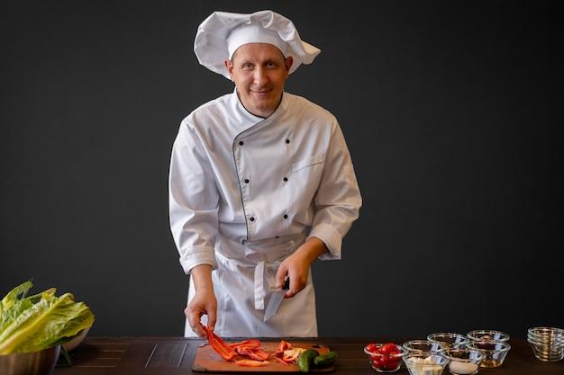 Шеф-повар среднего размера нарезает овощи