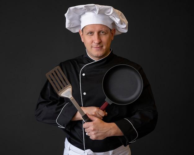 鍋とヘラでミディアムショットのシェフ