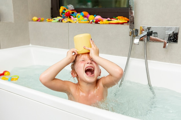 Medium shot child in the bathtub with toy