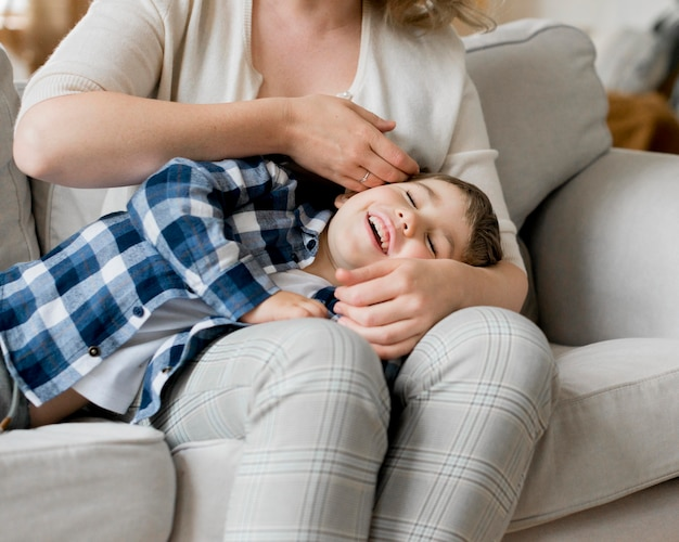 Medium shot of child sitting on mother's lap