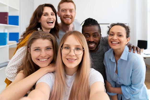 Коллеги со средним снимком, делающие селфи