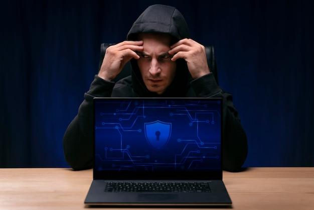 Средний снимок обеспокоенного хакера, сидящего за столом