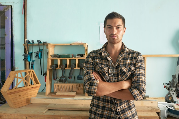 Medium shot of confident man standing arms folded in a carpentry shop