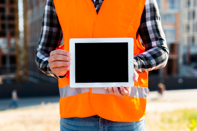 Medium shot construction engineer holding tablet