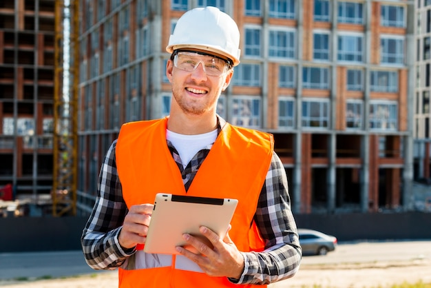 Medium shot construction engineer using tablet