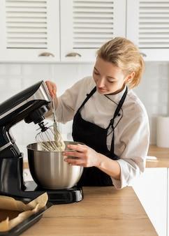 ミディアムショットの料理人がデザートを準備する