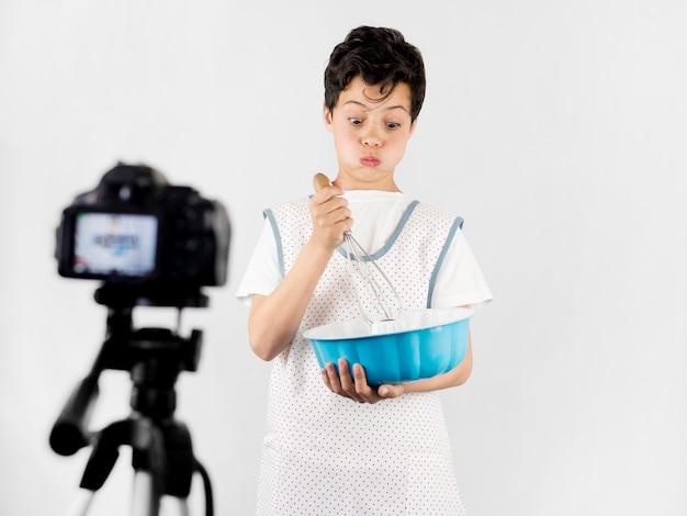 Bambino freddo della ripresa media che cucina sulla macchina fotografica
