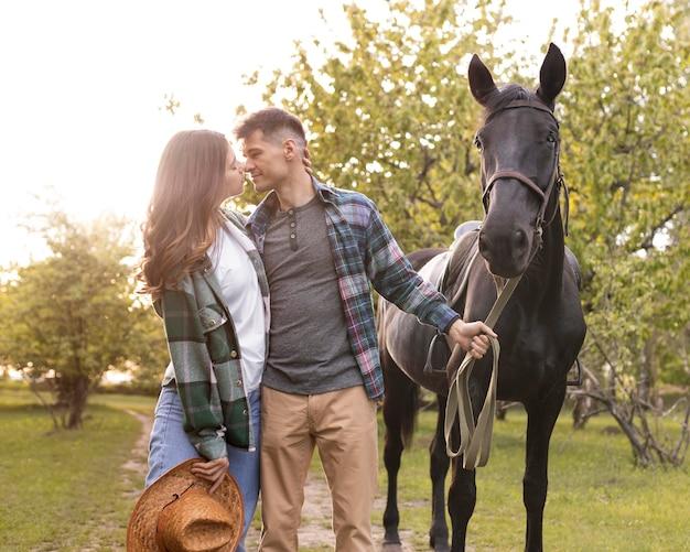 ミディアムショットのカップルと馬