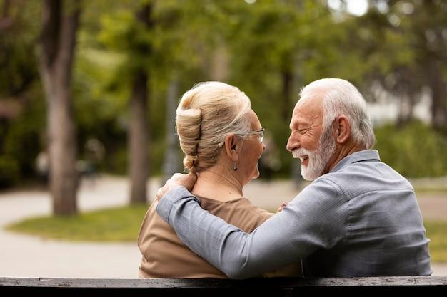 外でおしゃべりするミディアムショットのカップル