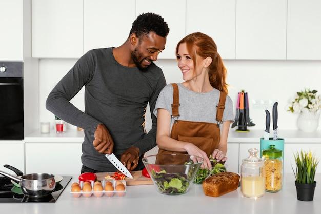 Coppie del colpo medio che cucinano insieme