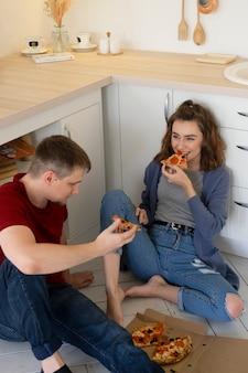 Пара среднего выстрела, едящая пиццу