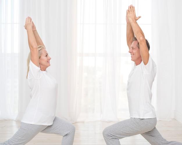 Medium shot couple exercising at home