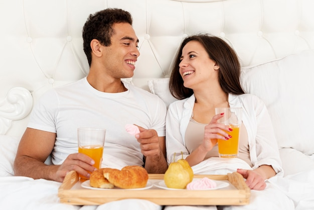 ベッドで朝食を持っているミディアムショットカップル