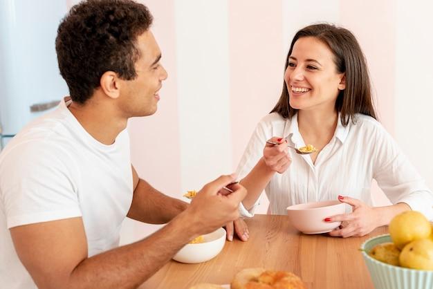 Coppie del colpo medio che mangiano prima colazione nella cucina