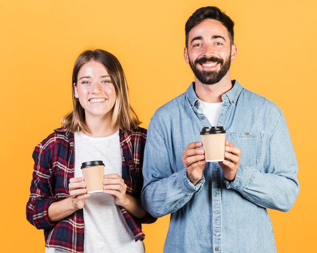 Medium shot couple holding coffee cups