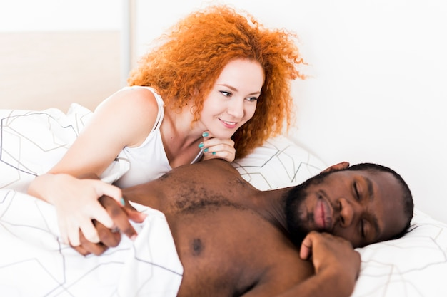 Medium shot of couple holding hands in bed