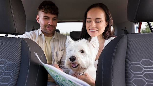 地図と犬を保持しているミディアムショットのカップル