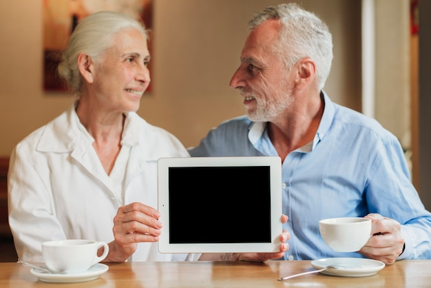 Medium shot couple holding a tablet mock-up