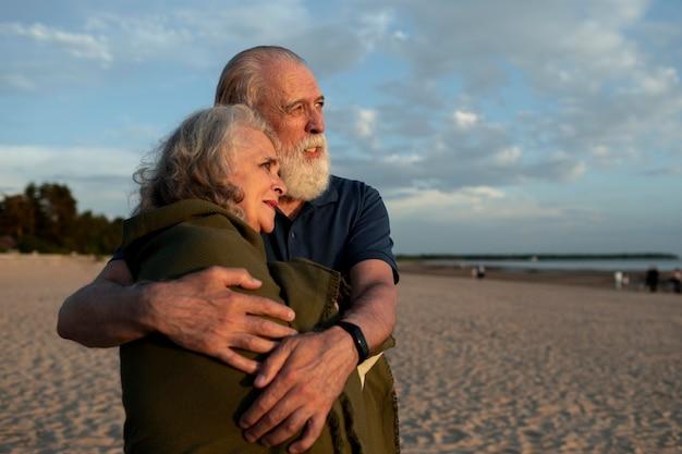 Coppia di colpo medio che si abbraccia in spiaggia?