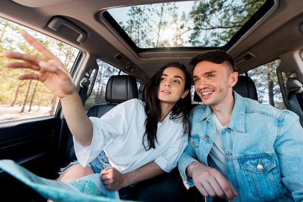 地図が付いている車のミディアムショットのカップル