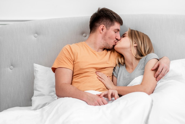 Medium shot couple kissing in the bedroom