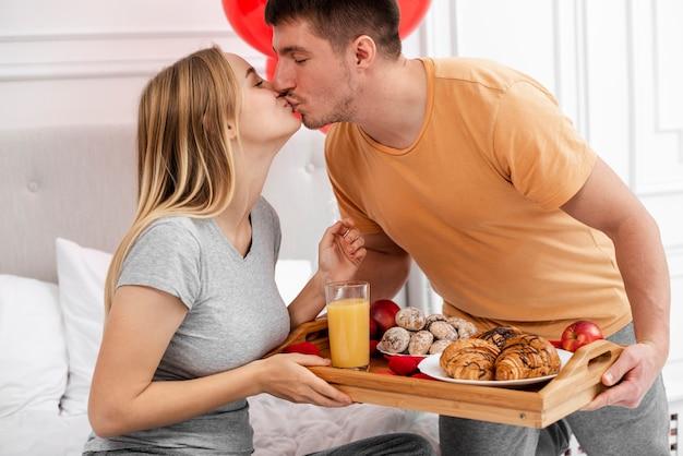 Medium shot couple kissing in bedroom