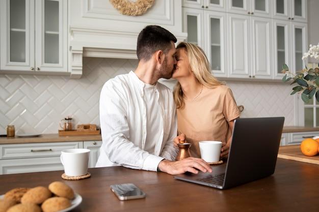 Пара среднего выстрела целуется на кухне
